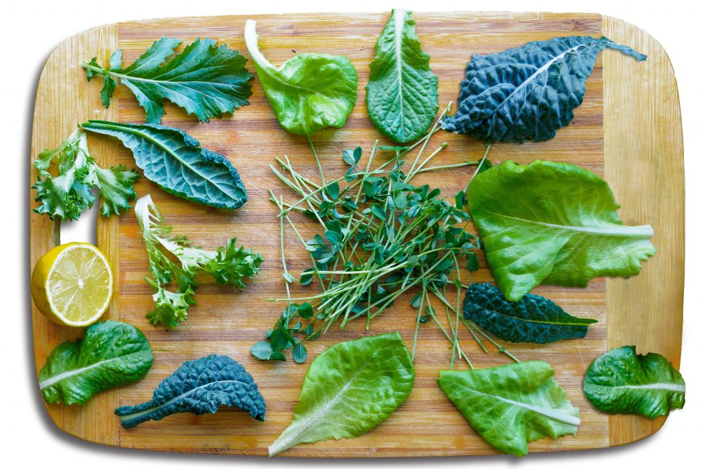 Leafy greens for a salad on  a cutting board. Kale, spinach, microgreens, and lemon