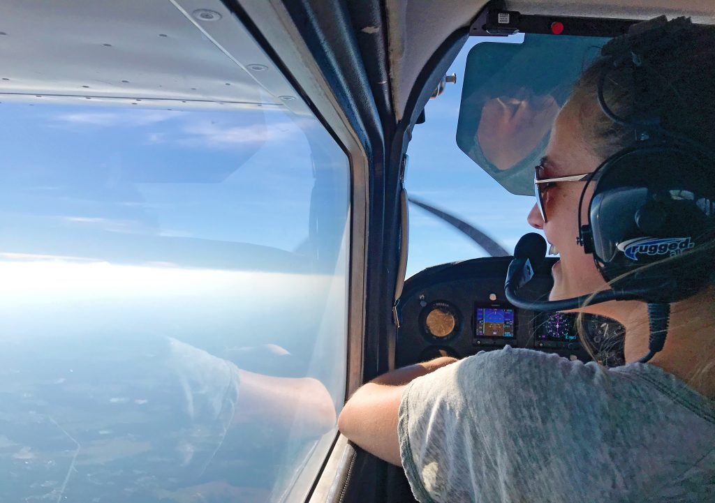 Opposite: Mary Kuehn looks out the window of a Cessna 172 on her way to Gilliam-McConnell Airfield in Carthage, North Carolina, for barbecue with friends in October 2019.  Photo by Danielle Donovan