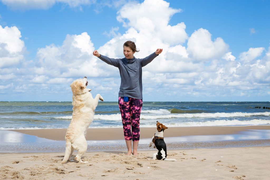 Woman training dogs on the beach