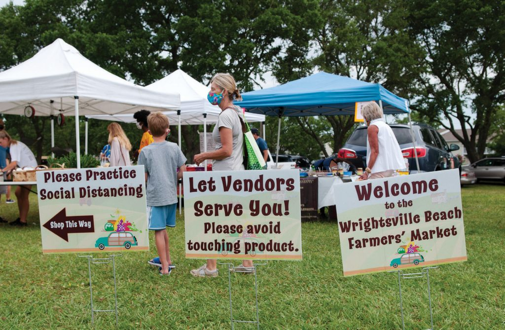 Signs remind shoppers of safety protocols at the Wrightsville Beach Farmers Market on June 29, 2020. | Allison Potter
