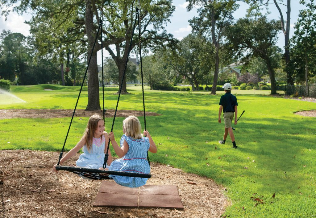 The Carroll girls, Harris and Drew, enjoy their time outdoors on a saucer tree swing in the backyard of their new home while their brother, Burton, heads out for putting practice. Photo by Allison Potter.