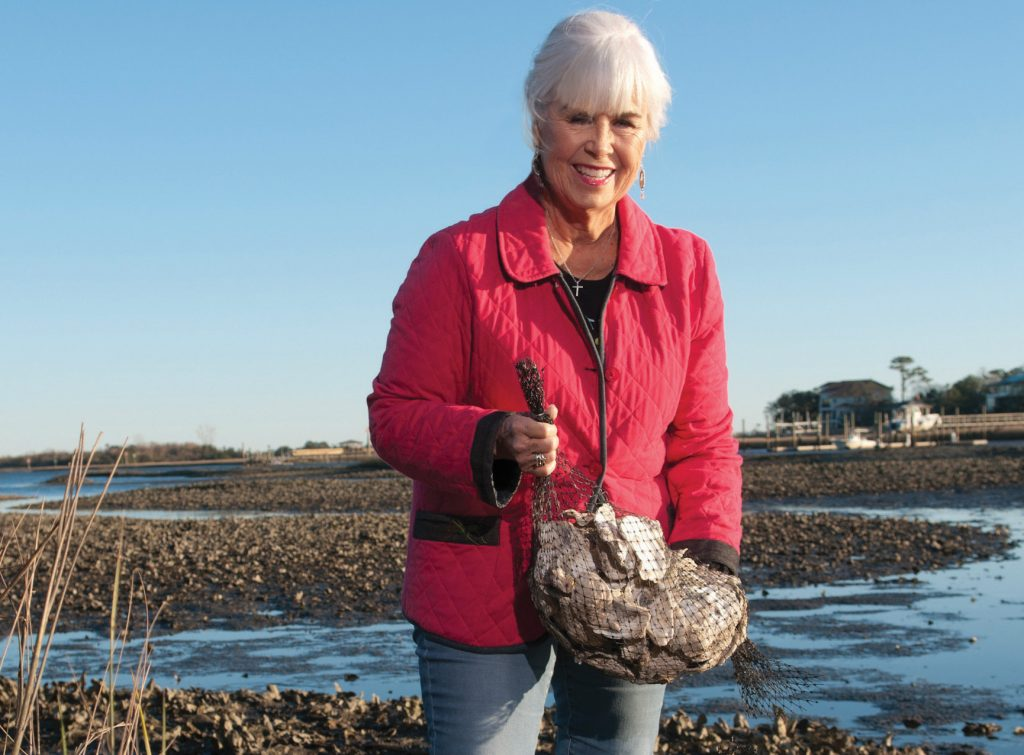 Pat Bradford holds a bag of recycled oyster shells on the edge of Bradley Creek at Airlie Gardens in 2019. WBM file photo.