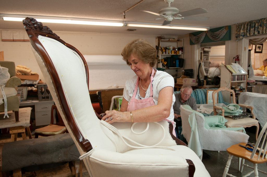Alma Fennell, owner of Drapery World, positions cording on a reupholstered Victorian chair. Photo by Allison Potter.