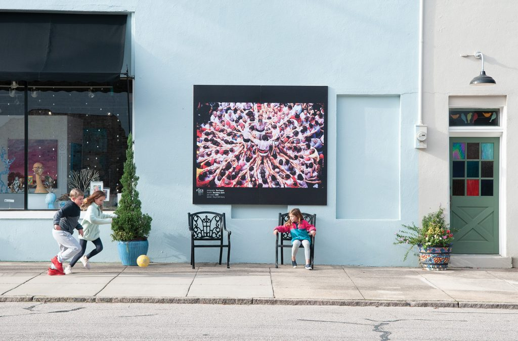 Children play in downtown Wilson under a photograph shot by Ron Cooper in Barcelona, Spain. Allison Potter