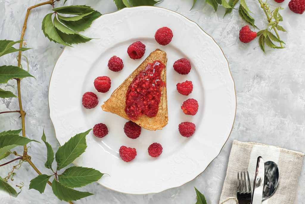 Pancakes with jam are located on a white plate, around the pancakes on a plate are fresh berries. Next to a glass of milk. The table is decorated with an ivy branch. Cutlery on a blue napkin. Breakfast, festive food. Gray background. View from above.