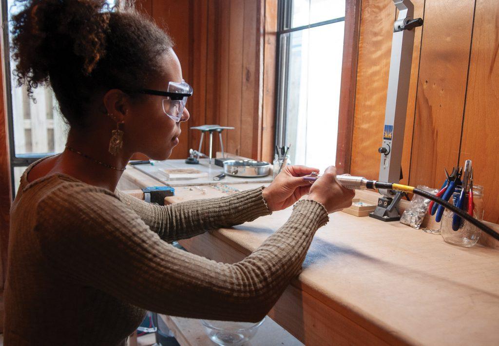 Ari Kwakye of Sea Bones Jewelry polishes rings in her Wrightsville Beach studio. Allison Potter