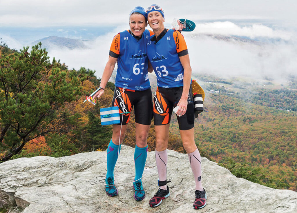 Jennifer Devers, left, and Bridget Phillips pause for a team photo at the top of Moore's Wall in Hanging Rock State Park during the 2017 SwimRun NC, the pair's first SwimRun event. Photo Courtesy of Jennifer Devers